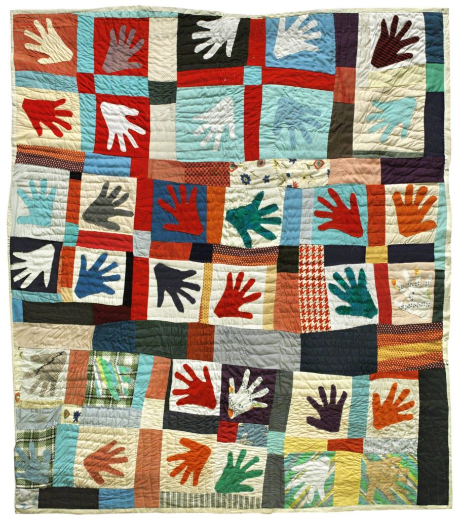 Image of a quilt with hand silohuettes in bright colors.