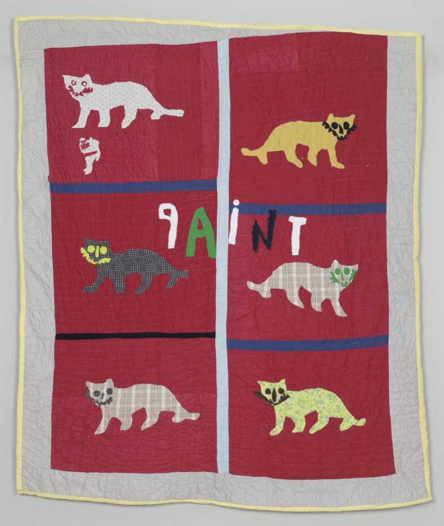 Image of a quilt with cats against red background and the word paint appliqued in the middle.