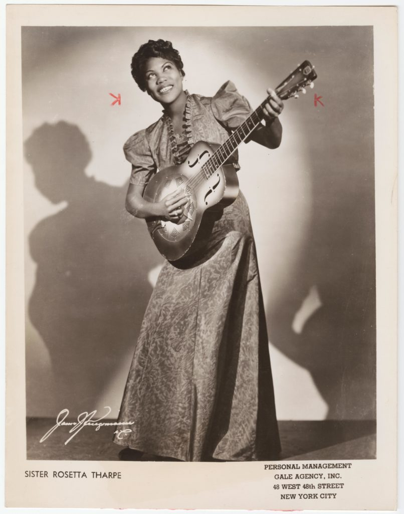 Untrimmed promotional image of Sister Rosetta Tharpe with guitar.