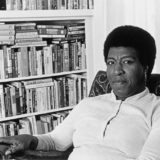 A black and white photograph of Octavia Butler seated at home in front of several bookshelves.