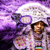Mardi Gras Indian dressed in a purple suit adorned with feathers, jewels, and beads.